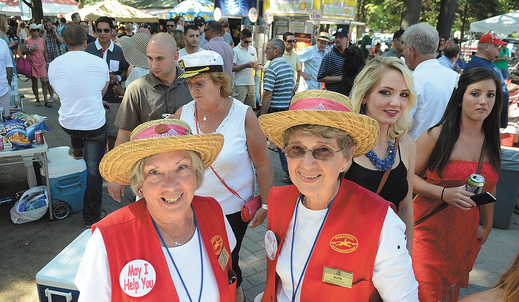 Description of . NYRA hospitality ambassadors Judy Hefter, left, and Ruth Mattiello wait to answer questions from track patrons on Travers day. Photo Ed Burke/SARATOGIAN 8/24/13