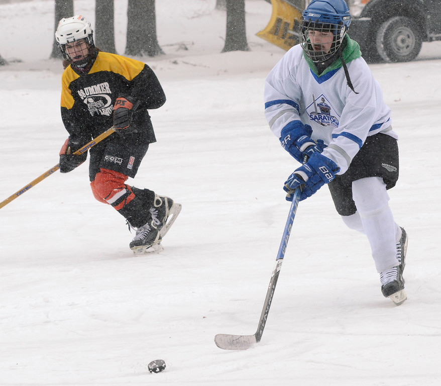 Description of . Ed Burke - The Saratogian 01/25/14 Former Blue Streak hockey player Chad Kelly, playing for team TCGU (This Could Get Ugly) is shadowed by Becky Jaiven of Schenectady of team Lucky Puck Saturday during the Saratoga Frozen Springs Classic Hockey Tournament at Saratoga Spa State Park.