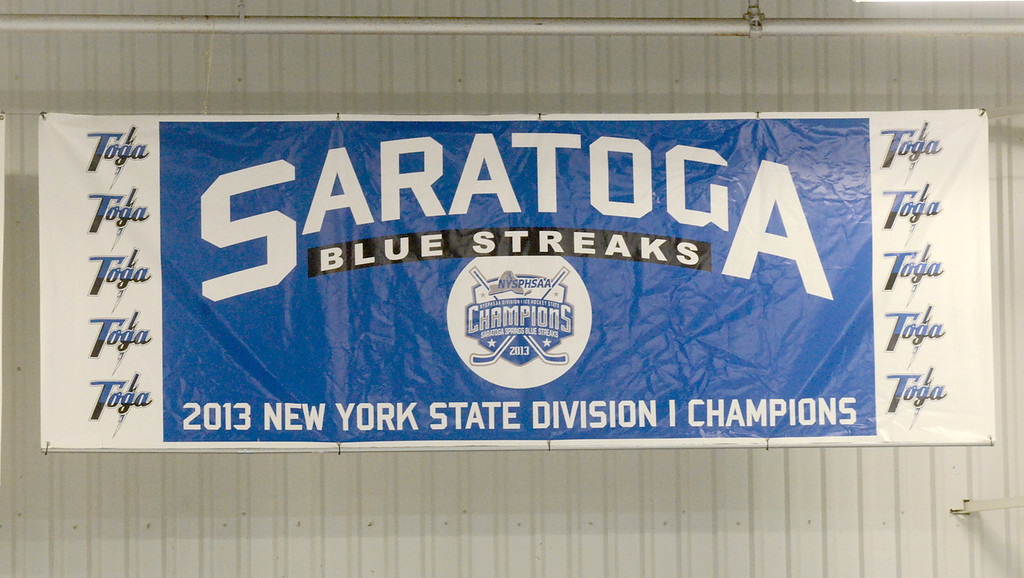 Description of . Ed Burke - The Saratogian 12/06/13 The Saratoga Springs Blue Streak varsity hockey team competed under a new banner unveiled Friday recognizing last year's state championship team. Saratoga was matched up against Mamaroneck in the first day of the Don Kauth Memorial Tournament.