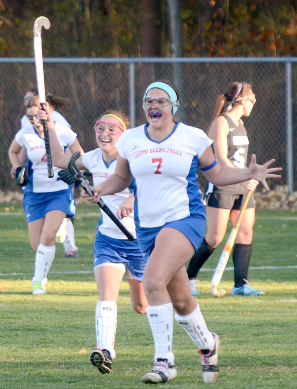 Description of . Ed Burke - the Saratogian South High's Emily Sharpe (7) and Nicole Crawford join the rest of the Bulldogs in celebrating Tuesday's varsity field hockey semi-final win over Glens Falls.