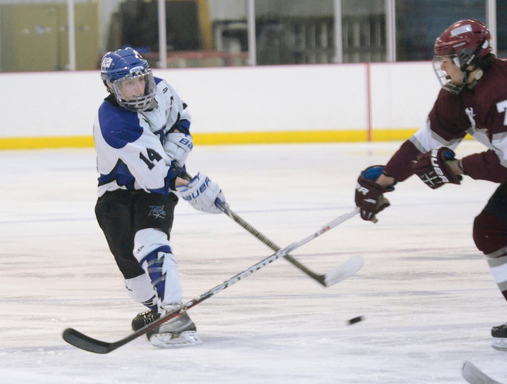 Description of . Ed Burke - The Saratogian 12/07/13 Saratoga's Drew Paterson shoots on goal as St. Joseph's Matt Ruggierio tries to block during Saturday's action in the Don Kauth Memorial Tournament at Saratoga Springs Ice Rink.