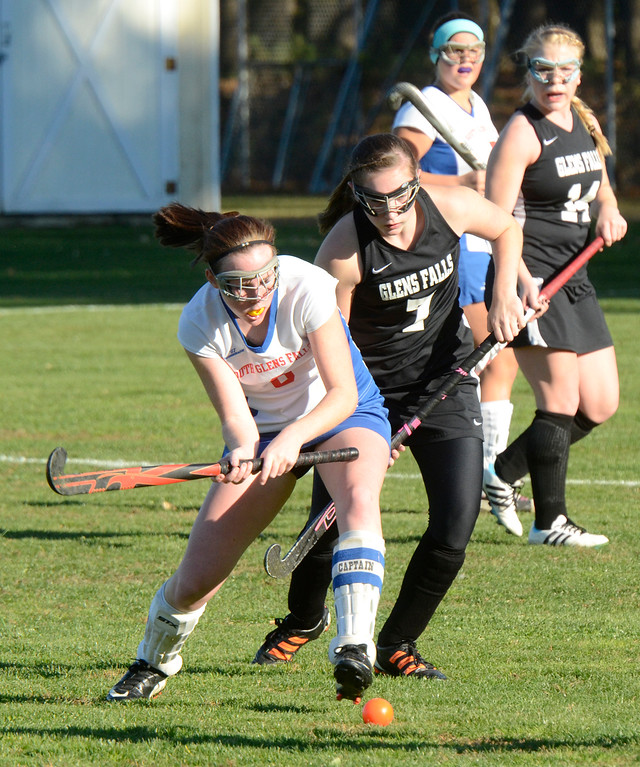 Description of . Ed Burke - the Saratogian South High varsity field hockey player Olivia Higgins winds up while pressured by Emily Haas during the Bulldogs 1-0 semi-final win over Glens Falls Tuesday at South Glens Fall High School.