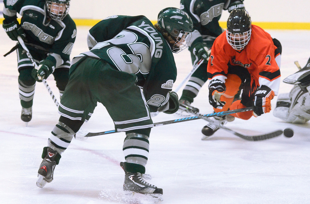 Description of . Ed Burke - The Saratogian 12/07/13 Shen's Nick Young shoots on goal as Mamaroneck defenseman Cooper Lavan closes in during Saturday's action in the Don Kauth Memorial Tournament at Saratoga Springs Ice Rink.