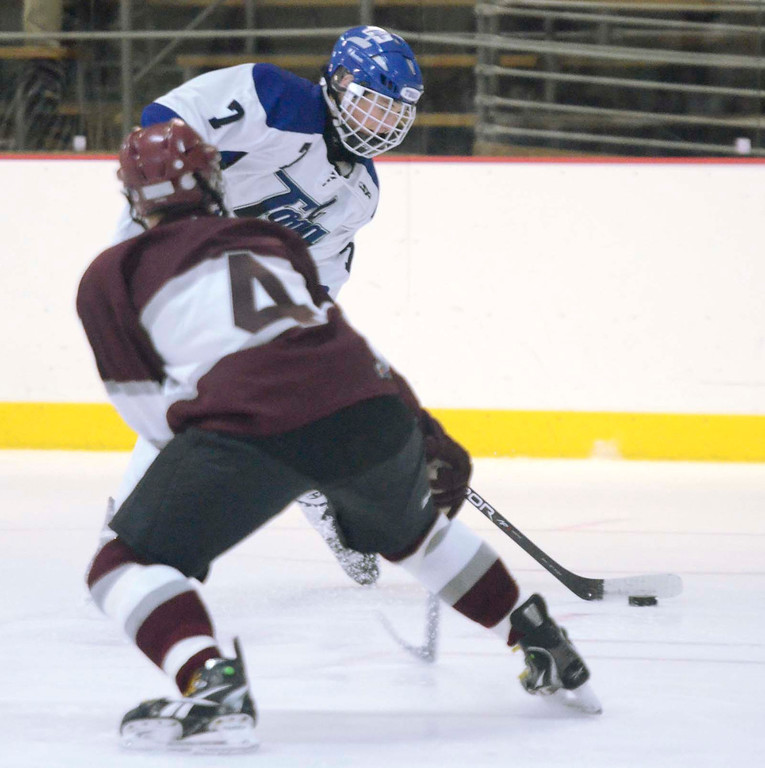 Description of . Ed Burke - The Saratogian 12/07/13 Saratoga's Devin Coffey scores on this shot as St. Joseph's Brad Kaminski tries to block during Saturday's action in the Don Kauth Memorial Tournament at Saratoga Springs Ice Rink.