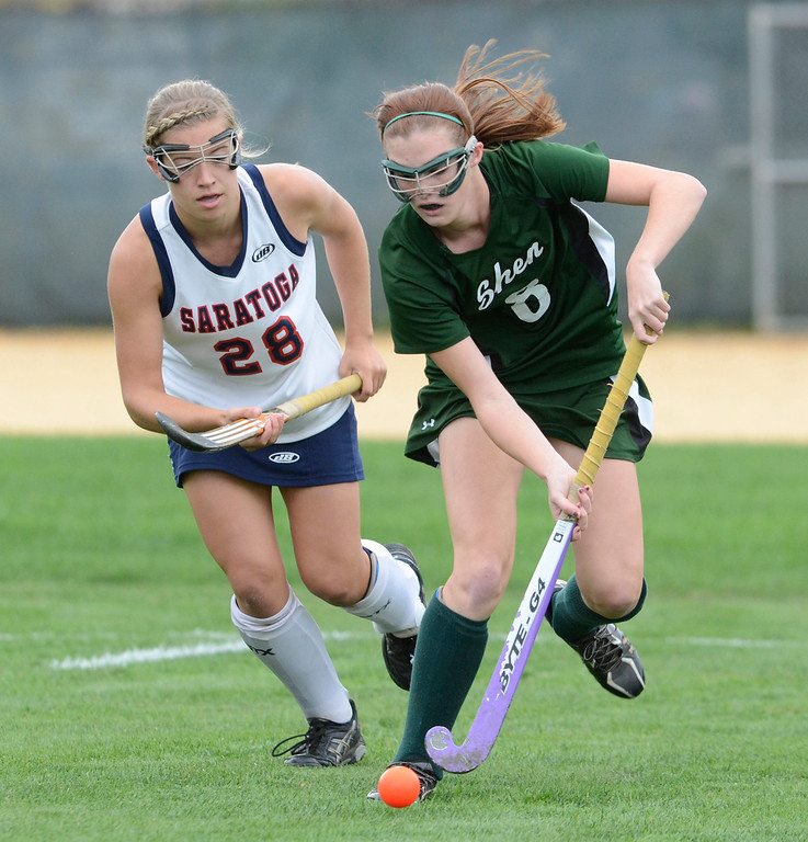Description of . Shen's Molly Hagen works to stay ahead of Saratoga defender Kelsey Briddell during Wednesday's varsity field hockey game at Saratoga. Ed Burke -  The Saratogian 10/16/13