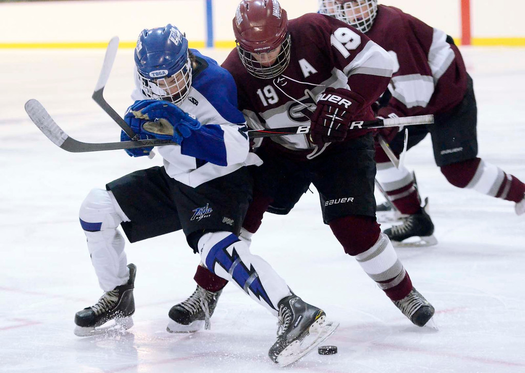 Description of . Ed Burke - The Saratogian 12/07/13 Saratoga's Josh Dagle tries to get his skate on the puck while battling St. Joseph's Nick Zenger during Saturday's action in the Don Kauth Memorial Tournament at Saratoga Springs Ice Rink.