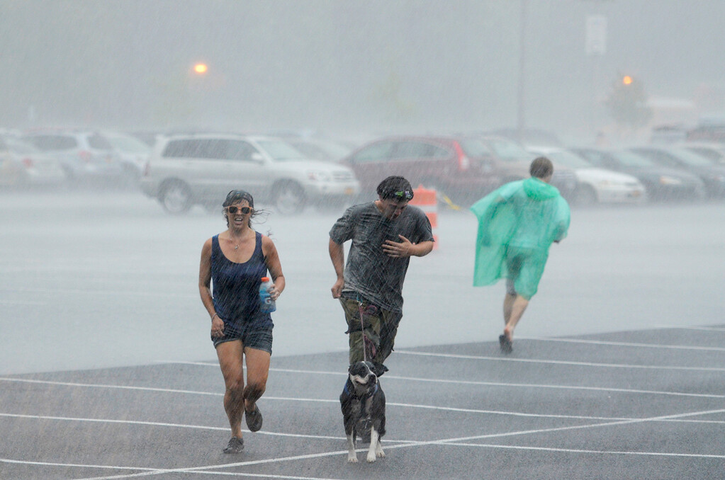 Description of . Erica Miller @togianphotog - The Saratogian:    On Thursday July 3rd 2014, Saratoga Springs was packed with thousands of Phish fans for their first of three concert nights at SPAC. Patrons get caught in the rain in the main parking lot at SPAC.
