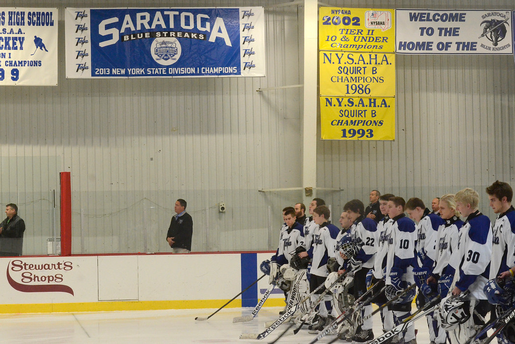 Description of . Ed Burke - The Saratogian 12/06/13 The Saratoga Springs Blue Streak varsity hockey team lines up for the National Anthem under a new banner, left, unveiled Friday recognizing last year's state championship team. Saratoga was matched up against Mamaroneck in the first day of the Don Kauth Memorial Tournament.