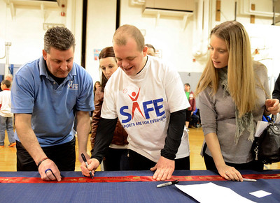 Ed Burke - The Saratogian 01/18/14 SAFE athlete Mike Lenigan signs a ribbon Saturday at Okte Elementary School in Clifton Park partnering the U.S. Navy with Sports Are For Everyone. Aside Lenigan, who has participated in the program for ten years, are his sister Julia Lenigan and SAFE coach and program director Frank Mancini. SAFE was founded in 1992 by Jim Fitzgerald to ensure those with special needs were able to participate in sports and build friendships and self-confidence.