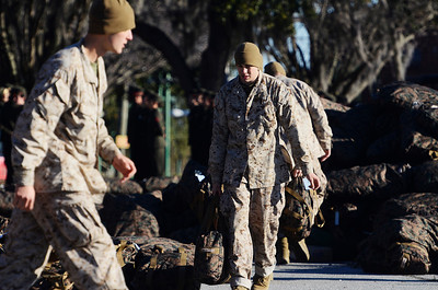 Erica Miller @togianphotog - The Saratogian:     In Parris Island at the Recruit Training Regiment Marine Corps Recruit Depot, as recruits wait in formation for the parade before they march on in front of their family and friends for graduation day on Friday  February 14th, 2014. Other lower recruits arrange their luggage before the parade started.
