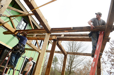 Erica Miller @togianphotog - The Saratogian:  On Friday morning, April 11th, 2014, in Saratoga Springs employees work on reconstructing an old barn, dating back to around 200 years old, on a property at 139 Meadowbrook Road. While creating an outside patio, Cory Tompkins (top right) and Stan Walczak (top left) move a beam for the roofing as Shannon Hazelton (ground level) helped.