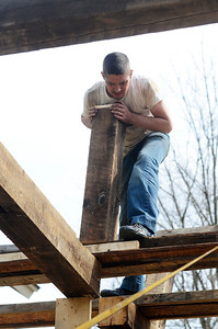 Erica Miller @togianphotog - The Saratogian:  On Friday morning, April 11th, 2014, in Saratoga Springs employees work on reconstructing an old barn, dating back to around 200 years old, on a property at 139 Meadowbrook Road. While creating an outside patio, Shannon Hazelton pushing in a supporting beam for the roofing.