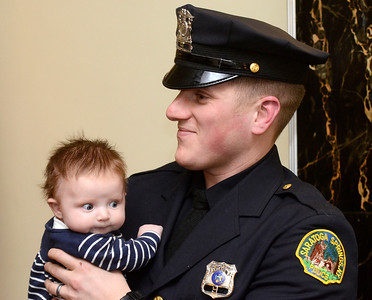 Ed Burke - The Saratogian 03/18/14 New Saratoga Springs Police officer Officer Wade Collins holds his three month old daughter Finley after being sworn-in with three others during Tuesday's city council meeting.