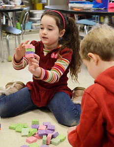 """Erica Miller @togianphotog - The Saratogian:  On Thursday morning, February 27th, 2014, kindergartners in Mrs. Allison Girard's classroom (maternity substitute teacher) at Lake Ave Elementary, students worked on building homes with play dough, sticks and glue. The class is the only pilot school in NYS for the pre-engineering program Project Lead the Way. The class read the """"three little pigs"""" and tried to build their own houses to test against a fan. Isabella Lamer glued together sponges for their house."""