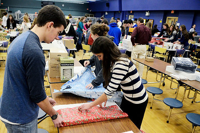 Erica Miller @togianphotog- The Saratogian.     The Saratoga Springs High School National Honor Society wrapped over a thousand presents Wednesday night. The Be A Santa to a Senior program, their 10th year, is put together through the Home Instead Senior Care. All gifts were requested through the seniors on a Senior Tree ornament.  Twins Cameron and Maya Bain, 16 year old Juniors, wrap a gift in the school cafeteria.SAR-l-SantaSenior2