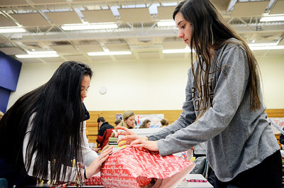 Erica Miller @togianphotog- The Saratogian.     The Saratoga Springs High School National Honor Society wrapped over a thousand presents Wednesday night. The Be A Santa to a Senior program, their 10th year, is put together through the Home Instead Senior Care. All gifts were requested through the seniors on a Senior Tree ornament.  Ellery Bianco (left) and Claudia Heritage 16 year old Juniors, wrap a gift in the school cafeteria.SAR-l-SantaSenior3
