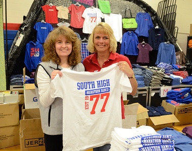 Ed Burke - The Saratogian 03/07/14 South High Marathon Dance volunteers Colleen Boyle, left, and Billie Jo Clute prepare to sell tee-shirts Friday night. Funds raised from the event, which began in 1977, will be distributed between 39 needy individuals, families and organizations.