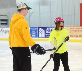 Ed Burke - The Saratogian 03/29/14 Hockey fan Lea Constantino of Saratoga Springs trades tips with Skidmore College hockey player T.J. Schneider during the Saratoga Ice Stars program Saturday at Saratoga Springs Ice Rink. The program, which is over 15 years old, is run by the Saratoga Springs Lions Club and gets physically challenged youths and adults on the ice to enjoy skating.