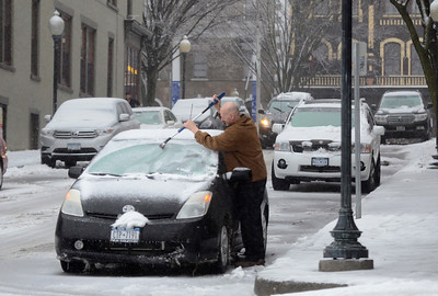 Ed Burke - The Saratogian 03/12/14 A driver scrapes ice and snow from his windshield on Phila St. during Wednesday's storm.