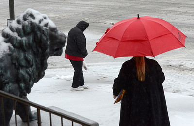 Ed Burke - The Saratogian 03/12/14 Hoods and umbrellas shield pedestrians from Wednesday's mixed percipitation as they take careful steps on Broadway near city hall.