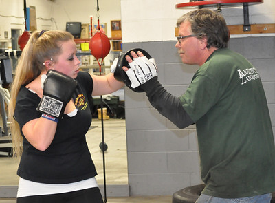 Photo Provided Erika Nichols, age 23, hits targets held by her father Michael Nichols. She is the granddaughter of Jack Nichols who helped start Saratoga Youth Boxing Association in 1976.
