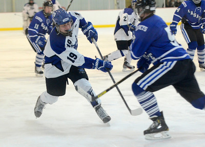 Ed Burke - The Saratogian 01/22/14 Saratoga's Issac Fisher shoots the puck as La Salles Mike DiBernardo closes in during Wednesday's matchup in Saratoga.