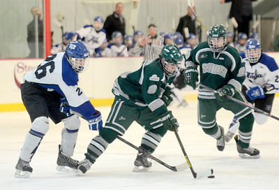 Ed Burke - The Saratogian 02/06/14; Shen's Tyler Lesniewski moves the puck as Saratoga's Elliott Hungerford challenges during Thursday's varsity hockey matchup at Saratoga Springs Ice Rink.