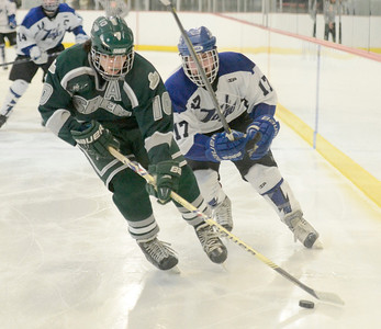 Ed Burke - The Saratogian 02/06/14; Shen's Peter Sacks moves the puck as Saratoga's Grayson Rieder closes in during Thursday's varsity hockey matchup at Saratoga Springs Ice Rink.