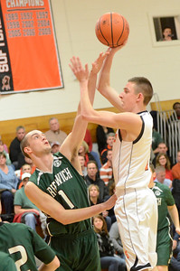 Ed Burke - The Saratogian 02/07/14; Schuylerville's Cameron Cook shoots over Greenwich defender Justin Carruthers during Friday's matchup in Schuylerville.