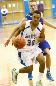 Ed Burke - The Saratogian 12/03/13 Saratoga's Camarin Ellis dribbles the ball as Queensbury's Adam Troelstra looks for the steal during Tuesday's game at Saratoga.