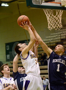 Ed Burke - The Saratogian 02/22/14 A shot by Saratoga Central Catholic's Evan Pescetti is blocked by Rensselaer's Tyler Oliver during Saturday's Section ll Class C quarter-final at Hudson Valley Community College.
