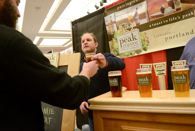 Ed Burke - The Saratogian02/22/14 Peak Organic Brewing Co. co-owner Craig Theisen serves a glass of his product during Saturday's Saratoga Beer Summit at the city center. The Portland, Maine based brewer sources some of his organic hops from Saratoga County.