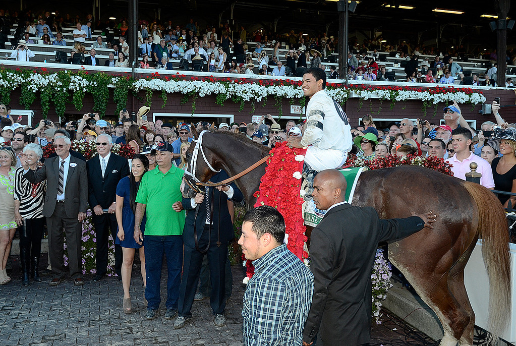 . Jockey Luis Saez sits atop Will Take Charge in the winners circle after beating the field in Saturday\'s Travers. Owner Willis Horton waves at left standing next to trainer D. Wayne Lukas. Photo Ed Burke/SARATOGIAN 8/24/13