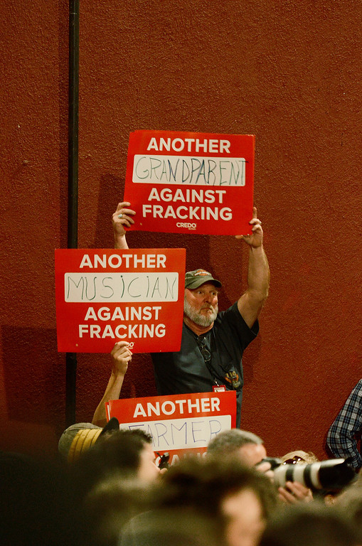 . Erica Miller - The Saratogian Farmers hold anti-fracking signs at the press conference to kick off the Farm Aid 2013 in Saratoga Springs on Sept. 21, 2013 at Saratoga Performing Arts Center.SAR-l-PressConf11